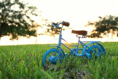 Blue vintage bicycle toy waiting outdoors at sunset light. Blue vintage bicycle toy waiting outdoors at sunset light stock photos