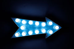Blue vintage bright and colorful illuminated display arrow sign. With light bulbs against a blue dark background Royalty Free Stock Photos
