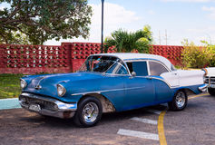 Blue vintage car. Vintage American car on a parking lot beside a palm tree in Cuba Stock Image