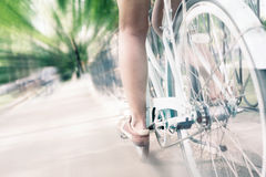 Blue vintage city bicycle, concept for activity and healthy lifestyle. Closeup of woman riding by blue vintage city bicycle at the city center with motion blur Royalty Free Stock Photos