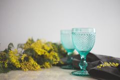 Blue Vintage Goblets and yellow mimosa flowers . Wineglasses on whight background stock images
