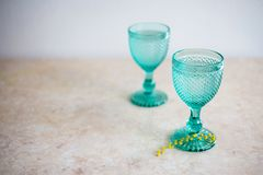 Blue Vintage Goblets and yellow mimosa flowers . Wineglasses on whight background royalty free stock photos