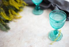 Blue Vintage Goblets and yellow mimosa flowers . Wineglasses on whight background royalty free stock image
