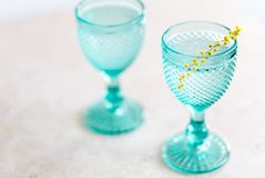 Blue Vintage Goblets and yellow mimosa flowers . Wineglasses on whight background stock photo