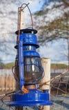 Blue vintage kerosene lamp on fence Stock Image