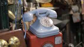 Dolly right shot of blue vintage rotary dial telephone for sale on a flea store