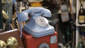 Dolly left shot of a blue vintage rotary dial telephone for sale on a flea store