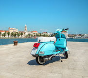 Blue vintage scooter on the waterfront. Blue vintage scooter stands on the waterfront on the background the city and the cruise ships in the sunny weather. Split Stock Photo