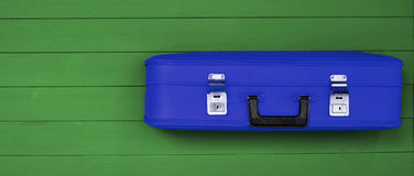 Blue vintage suitcases with black handle on the wooden green background. Retro travel luggage. Space for  text and design. Top view. Concept: tourism, travel Royalty Free Stock Image