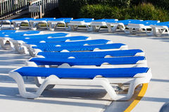Arc of Blue Vinyl Chaise Lounges Around Pool. Blue vinyl chaise lounges in a patio around a swimming pool Royalty Free Stock Images