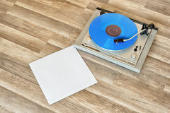 Blue vinyl record spinning on the turntable Stock Photos