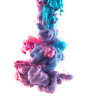 Blue and violet ink color drop underwater. Color drop underwater creating a silk drapery. Ink swirling underwater. Cloud of colorful shiny ink isolated on black royalty free stock photo