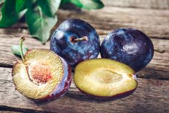 Blue and violet plums on wooden table. Blue and violet plums on wooden table Royalty Free Stock Photo
