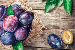 Blue and violet plums on wooden table. Blue and violet plums on wooden table Stock Image