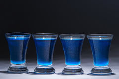 Blue vodka in four glasses Royalty Free Stock Photos