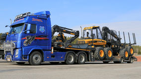 Blue Volvo FH13 Truck Hauling Ponsse Forestry Machinery Stock Image