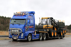 Blue Volvo FH13 Truck Hauls Ponsse Forwarder Royalty Free Stock Images
