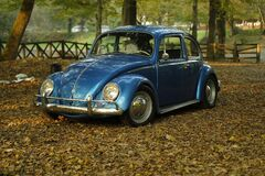 Blue VW Beetle in the park on Autumn leaves Stock Images