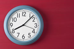 Blue wall clock on red grunge background. Royalty Free Stock Images