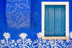 Blue wall, closed shutter of a window, with lace ornament Stock Photos