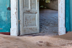 Blue wall and door of abandoned house. In sand. Shot in Kolmanskop ghost town, Namibia Stock Image