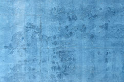 Blue Wall Flaking. Blue  paint on an exterior wall cracked and flaking to reveal old concrete beneath Royalty Free Stock Image