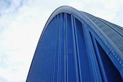 Blue wall of the hangar. Fragment blue ribbed metal roof on a background of  sky Stock Photos
