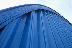 Blue wall of the hangar. Fragment blue ribbed metal roof on a background of  sky Stock Images