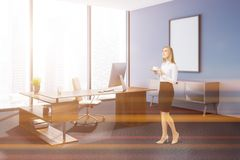 Blue wall manager office corner, poster, woman. Blonde businesswoman in modern manager office corner with a carpet on floor, blue walls, a stylish computer table royalty free stock photos