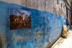 Blue Wall in the Medina. A blue wall with a classic Beduin fighting scene in the Medina of Fez, Morocco royalty free stock image