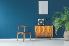 Blue wall and vintage decor. Stylish apartment interior with blue wall decorated in vintage style with wooden cupboard,chair, mock-up poster and tropical potted Stock Image