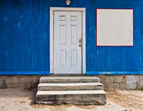 Blue Wall with White Door and Blank white sign Royalty Free Stock Images