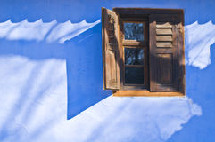 Blue wall with window. Rural house with blue wall and wood window Stock Photos