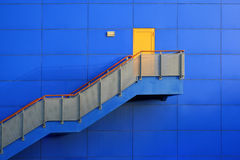 Blue wall and yellow door on top Stock Photography