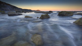 Blue water. The blue water rushes by large boulders at sunset Royalty Free Stock Photos