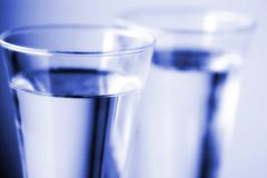 Blue Water. Two glasses of drinking water close up with intentional shallow depth of field and blue tint Stock Image
