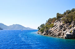 The blue water of the Aegean Sea off the coast of a rocky island Stock Images