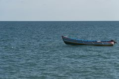 Blue water and alone boat Stock Photos