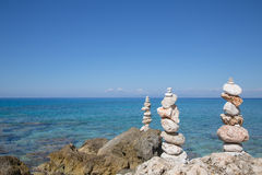 Blue water background with a stone pyramid. Royalty Free Stock Photo