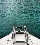 Blue water and boat ladder Royalty Free Stock Photo