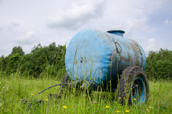 Blue water cistern drink for farm animal in meadow Royalty Free Stock Photo