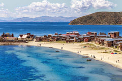 Blue water and coast of Titicaca lake, boats, walking people and Stock Photo
