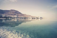 Blue water in the dead sea in the foreground on the background of the resort town of Ein Bokek in the middle of the desert in. Blue water dead sea in the royalty free stock image
