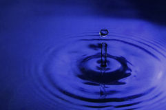 Blue water drop. A water drop in blue fluid with back light and some reflections Stock Photography