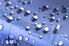 Blue water droplets. Close up of water drops on a rolled up newspaper wrapped in plastic through blue filter Royalty Free Stock Photo