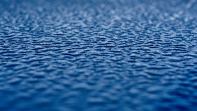 Blue Water Droplets on Metal Surface. Many water droplets in blue on a shiny smooth metal surface Stock Photo