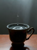 Blue water drops, splashing in the vintage cup. Classic wooden table. Frozen motion. soft focus, macro view Stock Photo