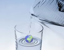 Blue water earth. A globe in a glass of water with water pouring on top Royalty Free Stock Photo