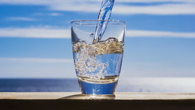 Blue water is flowing into the glass forming bubbles and splashes stock video footage