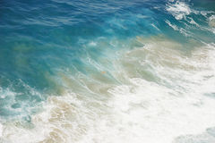 Blue water with foam at the ocean shore Royalty Free Stock Images